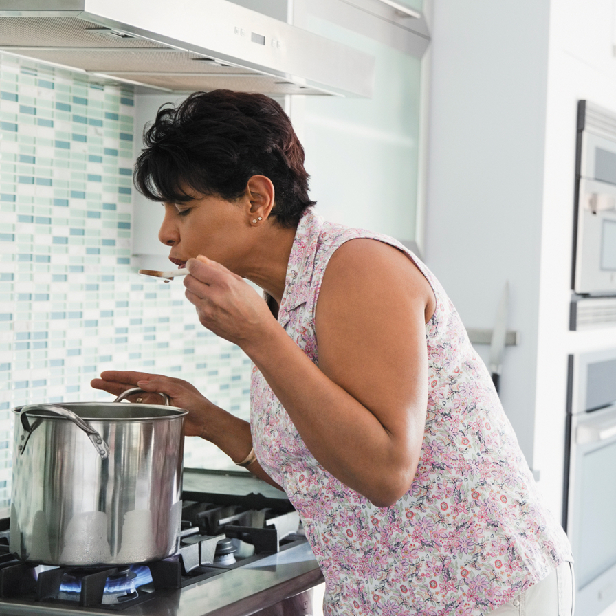 Woman tasting cooking soup